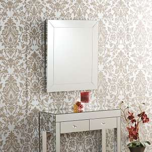 Elegant frameless wall mirror above a mirrored accent table